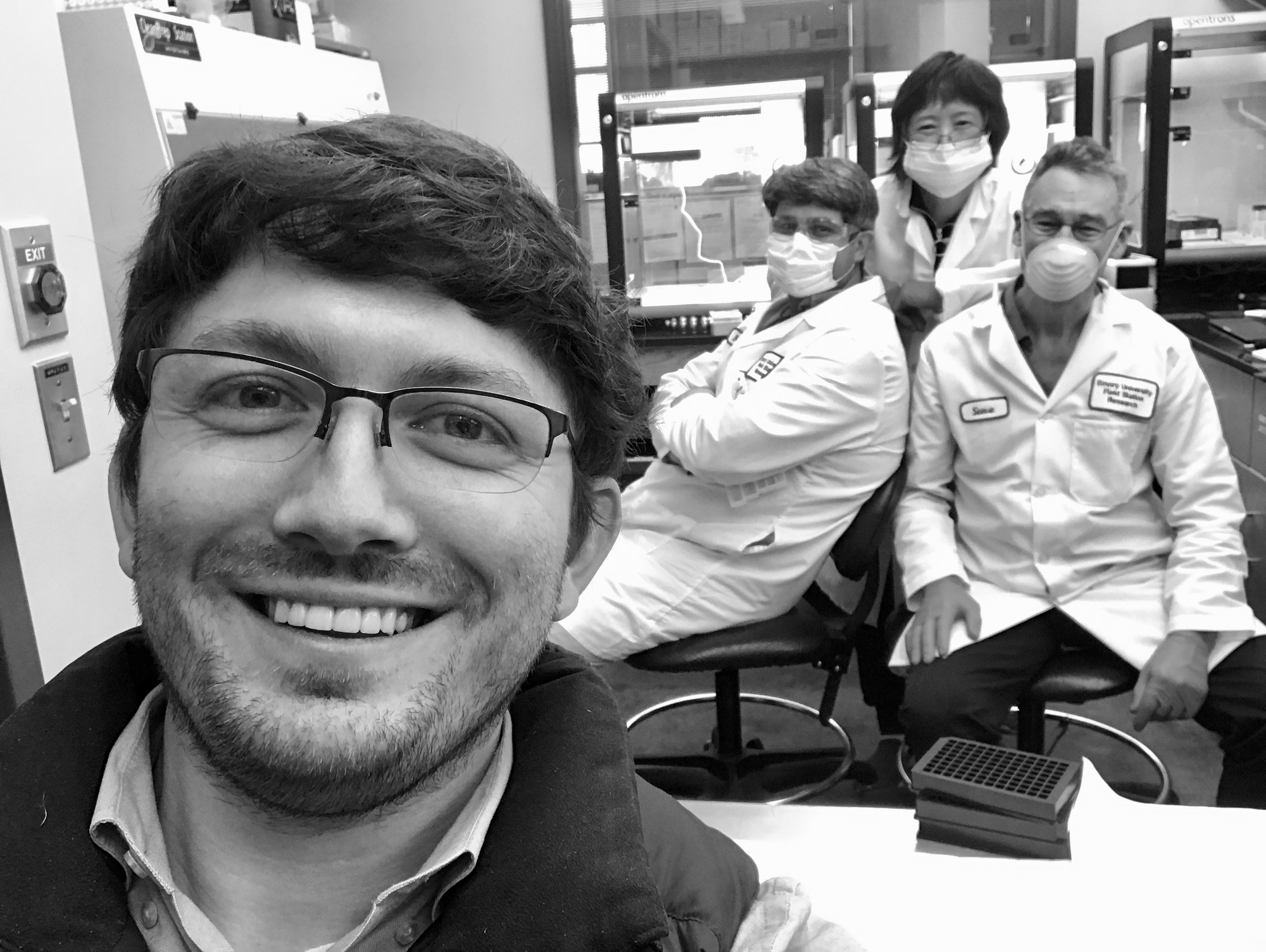 Adam Ericsen (front) in his lab with his 3 OT-2 and lab members Nathan Gullicksrud, Steven Plonk, and Yuhui Wu (l-r). CREDIT: Adam Ericsen